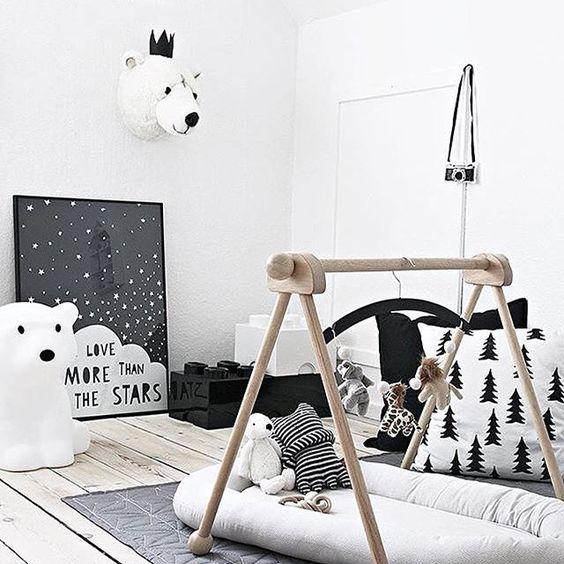 un cameretta nordico con una palestra per bambini, opere d'arte, un tappeto e teste di orso giocattolo per renderlo più suggestivo