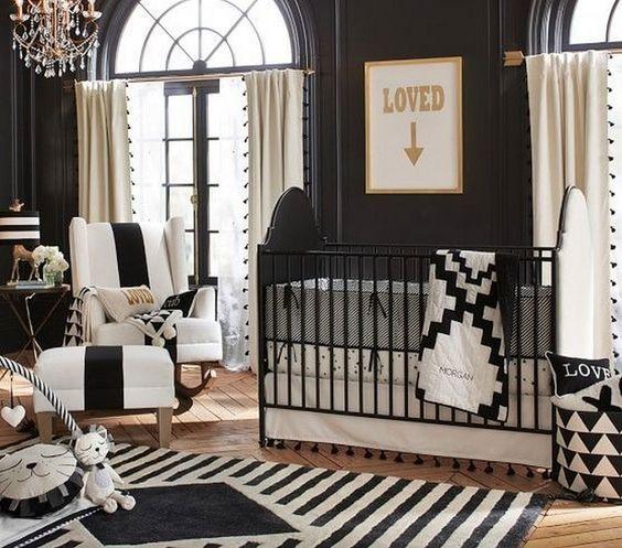 un raffinato cameretta con tante stampe, un lampadario di cristallo, una culla in bianco e nero e splendidi mobili