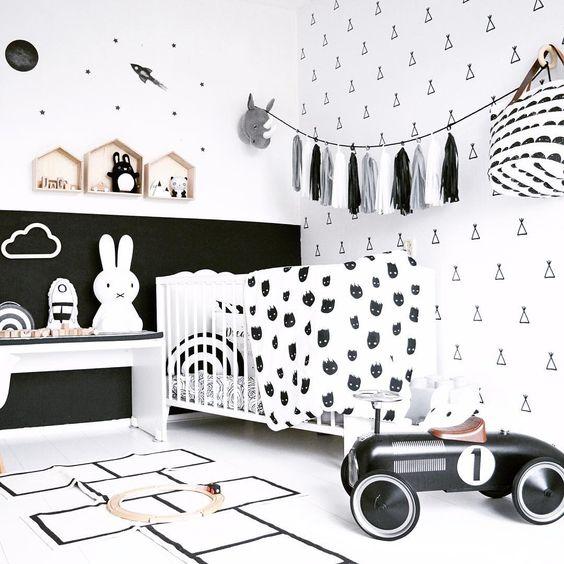 un elegante cameretta bianco e nero con mobili monocromatici, una ghirlanda di nappe, una culla bianca e molte stampe