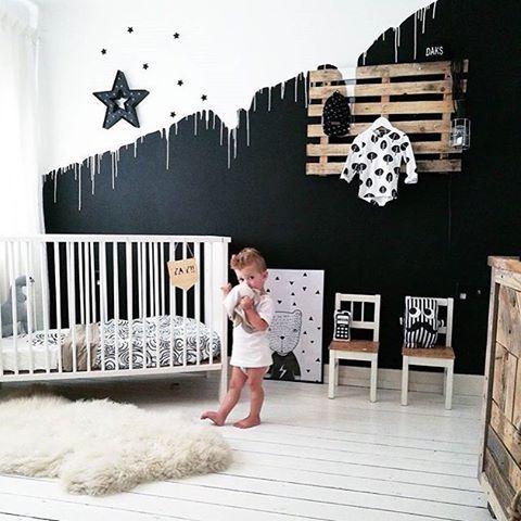 un elegante spazio in bianco e nero con un muro di accento, un appendiabiti per pallet, una culla bianca e alcuni tocchi più monocromatici