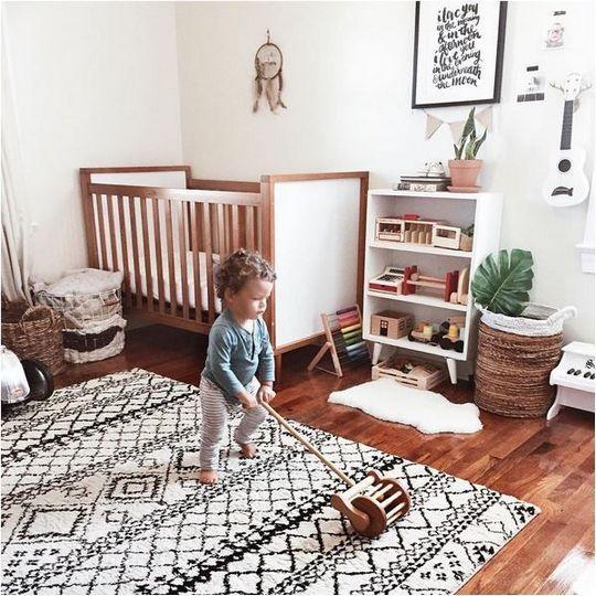 un cameretta boho con un tappeto decorato, cestini, un acchiappasogni sul muro e alcune cose semplici