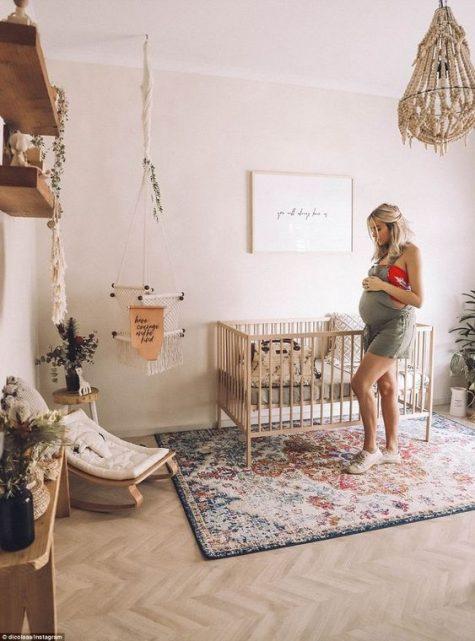 un cameretta boho con un tappeto boho, un lampadario di perline, una sedia a dondolo per bambini, piante in vaso appese