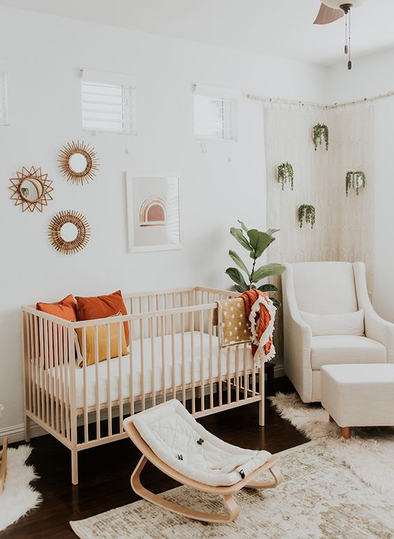 un cameretta boho chic con piante in vaso, una culla in legno e una piccola sedia a dondolo, un muro della galleria e alcuni tappeti boho