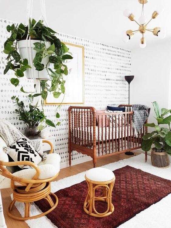 un luminoso cameretta boho moderno con una culla vintage, sedie in rattan, tappeti boho, vegetazione in vaso e un elegante lampadario