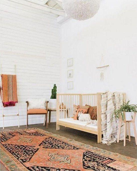 un cameretta dallo spirito libero con un tappeto boho, una culla di legno, piante in vaso e tocchi di eco-pelliccia qua e là