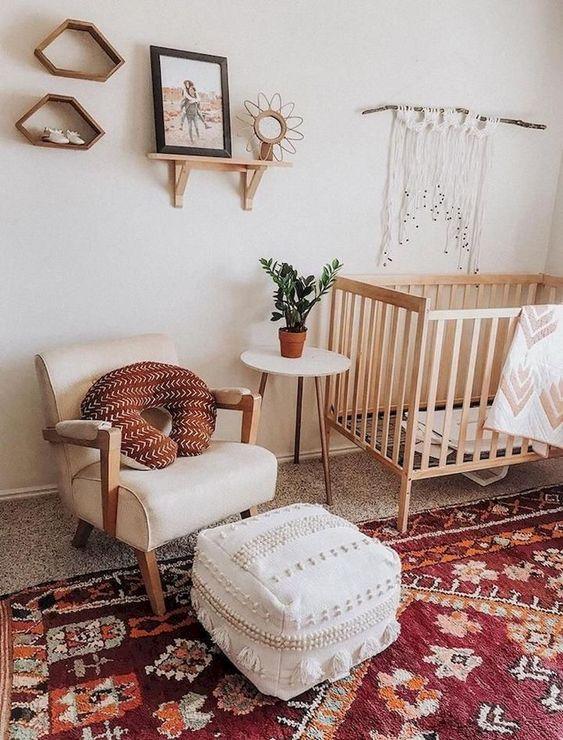 un luminoso cameretta boho con un tappeto boho rosso, un pouf marocchino bianco, macramè, scaffali della metà del secolo e una sedia chic