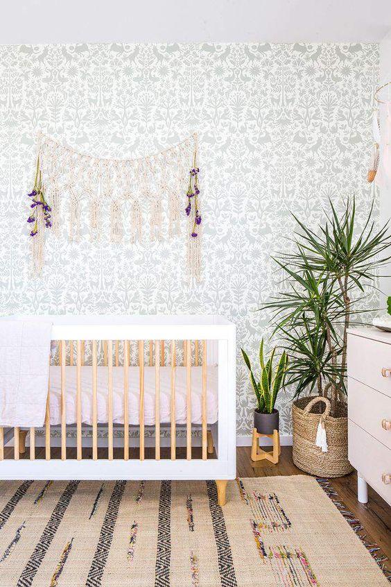 un grazioso cameretta boho con un muro di carta da parati botanica, un tappeto boho, una culla, macramè e vegetazione in vaso