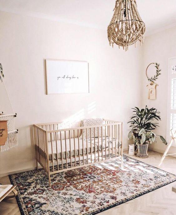 un cameretta boho pieno di luce con un lampadario di perline, un tappeto boho, vegetazione in vaso e un'opera d'arte minimale