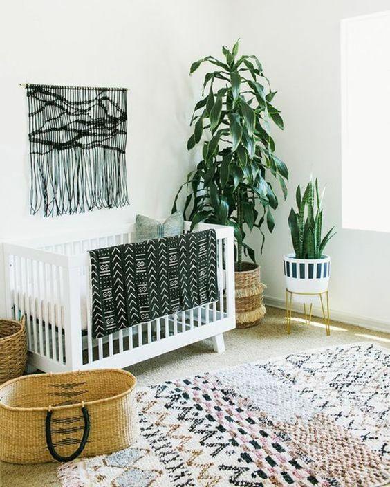 un cameretta boho monocromatico con un macramè nero appeso, un tappeto stampato, una coperta con stampa folk e piante in vaso
