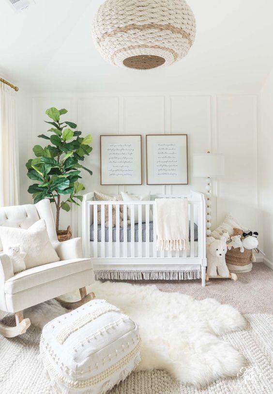 un celeste cameretta cremoso con una lampada di vimini, un tappeto in pelliccia sintetica, una sedia a dondolo, una culla bianca e un tappeto in maglia più un pouf marocchino