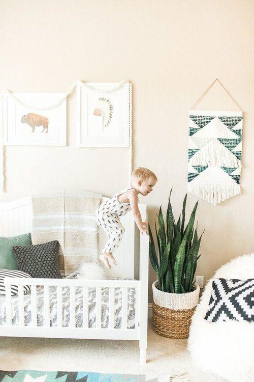 un cameretta boho neutro con un segno intrecciato, una galleria a parete, una fioriera a cesto e un grande e soffice pouf