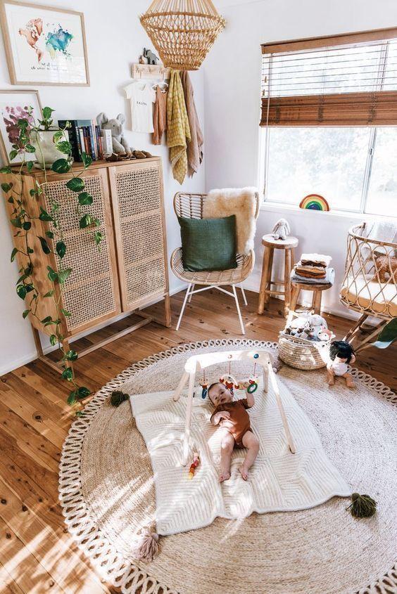 un cameretta boho dai colori caldi con un comò in vimini, un tappeto di iuta, una culla in rattan, mobili in legno e rattan e vegetazione