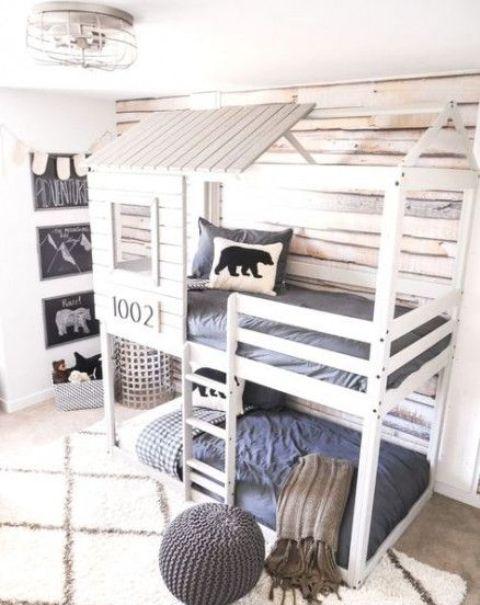 un letto a castello a forma di casetta per due, luci incorporate e una scala per raggiungere il letto superiore