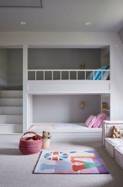 una stanza minimalista con letti a castello, una scala e piccole lampade da parete e mensole per la conservazione