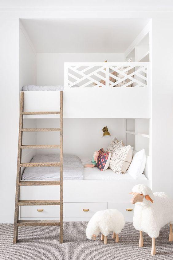 letti a castello bianchi da incasso con scala in legno, ringhiera accattivante, lampade da parete e cassetti portaoggetti nel letto inferiore