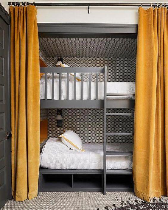 letti a castello grigi con scala matematica e ripostiglio sotto il letto, tende senape e lampade da parete sopra i letti