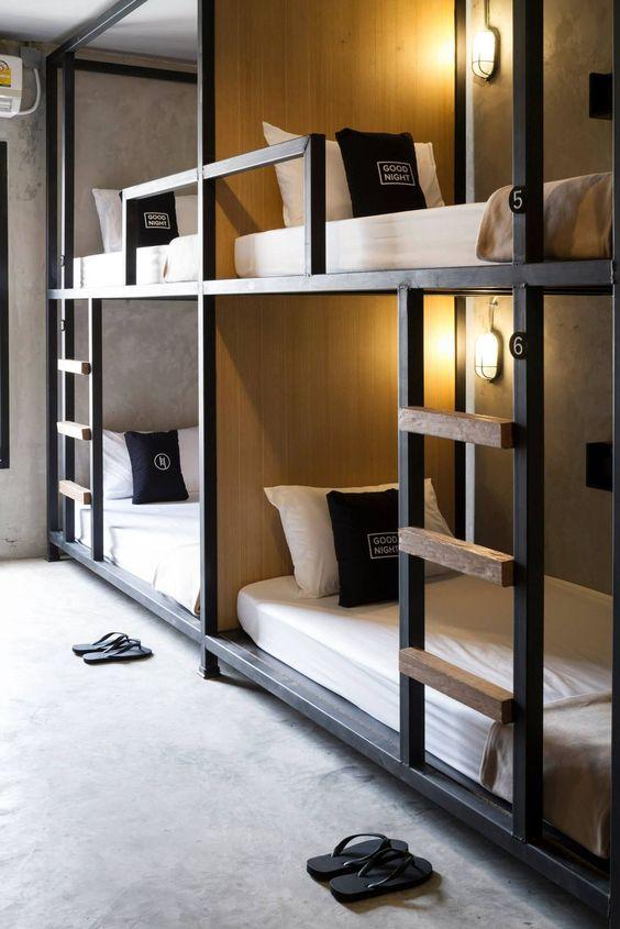 eleganti letti a castello industriali in metallo e legno, con lampade da parete e scale per raggiungere ogni letto superiore