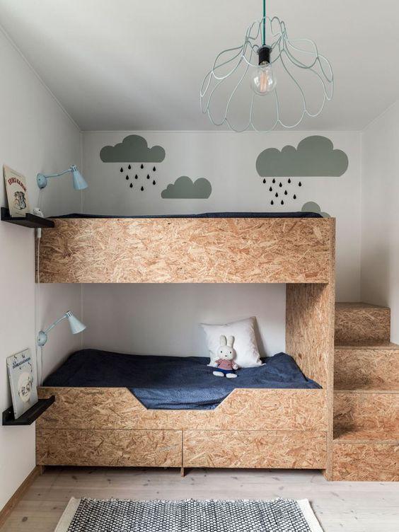 letti a castello in compensato con cassetti portaoggetti e applique blu per una stanza eccentrica e divertente