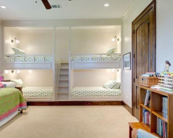 letti a castello per bambini per quattro persone, con applique e una scala singola tra i blocchi del letto