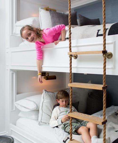 un letto a castello per bambini allestito con applique e una scala di corda per raggiungere ogni posto letto