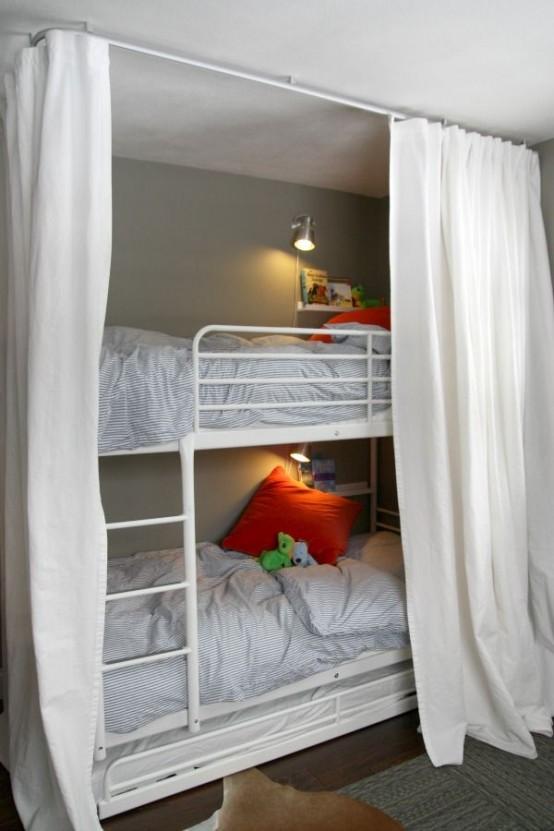 un letto a castello per bambini in metallo bianco con una scala attaccata e applique da parete più tende per mantenere privati gli spazi per dormire