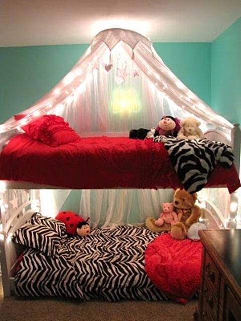 un letto a castello per due persone, una lampada da parete singola sopra il letto superiore e un baldacchino per un tocco sognante
