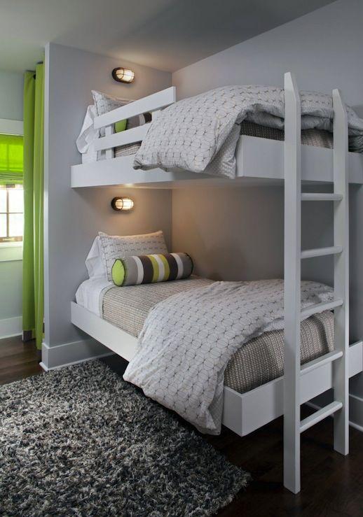 un moderno letto a castello bianco con una scala bianca, piccole lampade da parete e tocchi a strisce