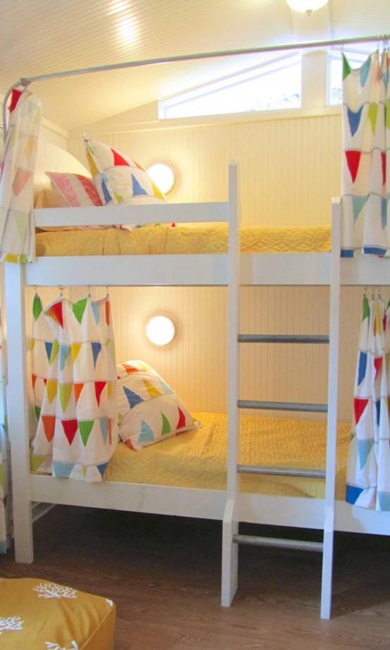 un grande letto a castello bianco con una scala, lampade da parete e biancheria da letto colorata con varie stampe