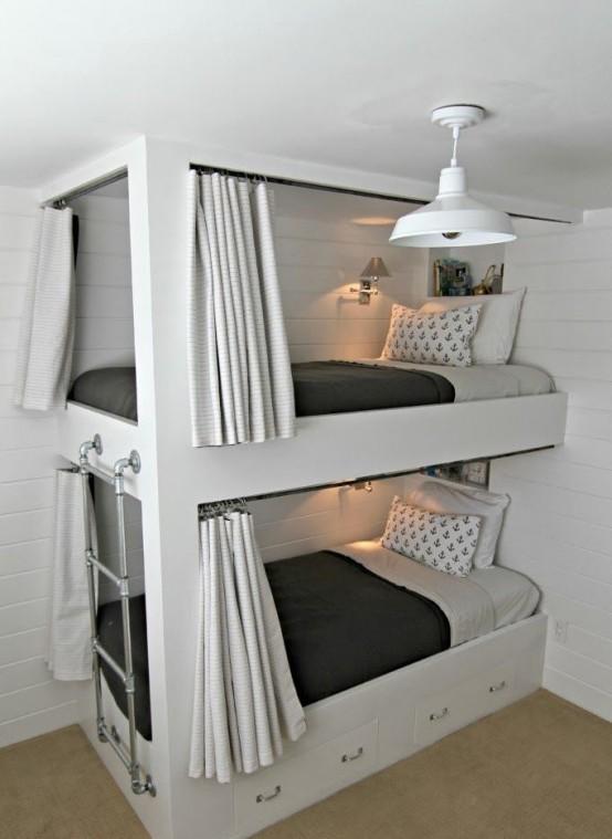 un moderno letto a castello con una scala in metallo attaccata e cassetti integrati nel letto inferiore per riporre gli oggetti e tende per la privacy