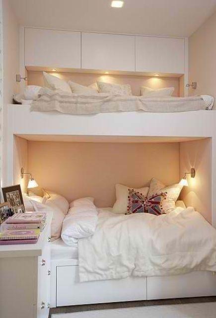 un letto a castello bianco minimalista con un elegante spazio di archiviazione con luci integrate e applique sopra il letto inferiore