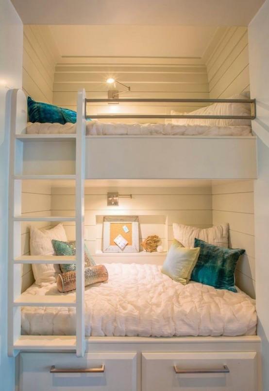 accoglienti letti a castello incorporati in bianco con applique sopra ogni letto e una singola scala per raggiungere la zona notte superiore