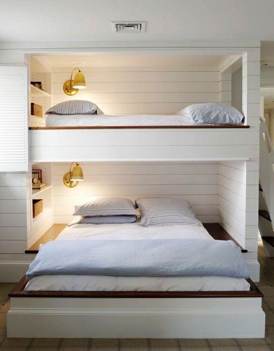 un unico letto a castello per due persone con un letto a scomparsa nella parte inferiore, applique e mensole incorporate sopra i letti