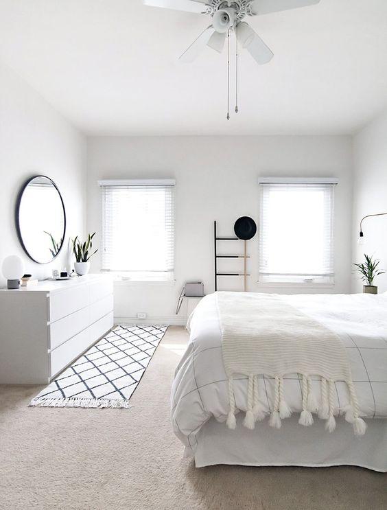 una camera da letto bianco puro con un tocco nordico, una credenza elegante bianca e sfumature alle finestre