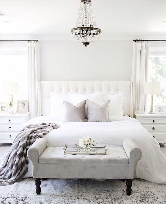 una camera da letto chic in colori neutri, con pareti bianche, un letto imbottito bianco e una panca imbottita grigia