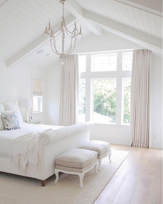 una camera da letto bianca molto fresca con tende e sgabelli color crema, un elegante lampadario e un letto imbottito bianco