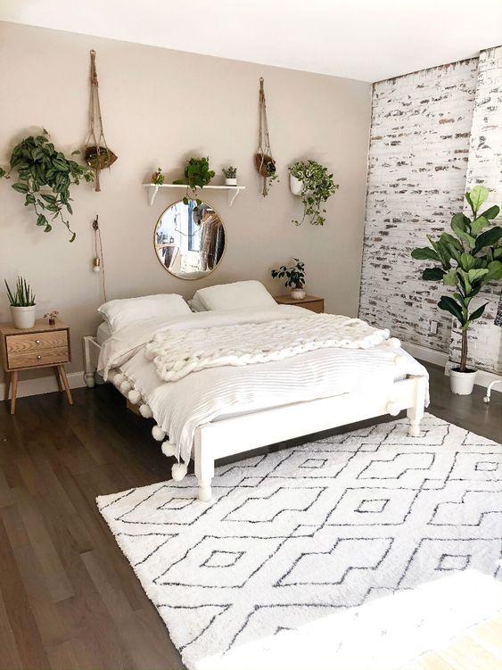 una camera da letto minimalista boho neutra in bianco e grigio più mobili in legno dai toni chiari