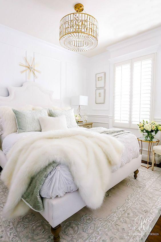 una camera da letto glam neutra con pareti bianche, un lampadario di cristallo di tendenza e biancheria da letto chic più pelliccia sintetica