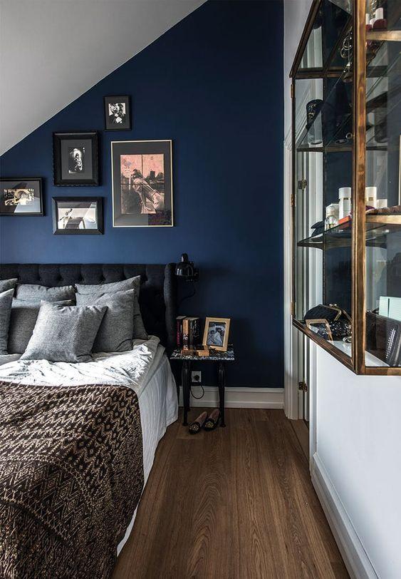un'epica camera da letto mansardata blu scuro con un letto imbottito scuro, biancheria da letto neutra e un pensile in vetro