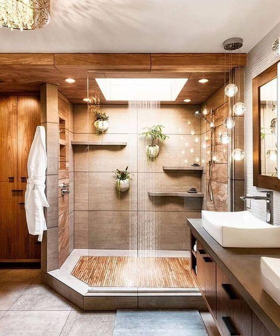 uno spazio doccia dai colori caldi simile a una spa fatto in neutri e con una doccia a pioggia e luci per il relax