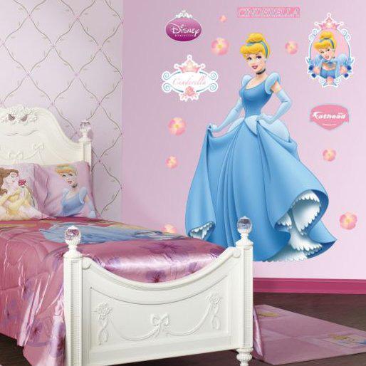 una cameretta per bambini a tema principesse Disney realizzata in rosa, con opere d'arte sul wlal e un letto fatto con lenzuola rosa