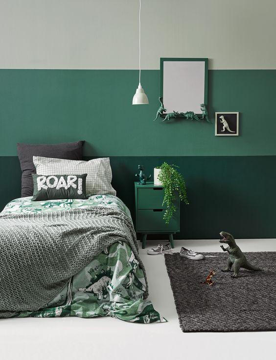 una divertente camera a tema verde menta e dinosauro con vegetazione, dinosauri e biancheria da letto divertente è perfettamente in stile