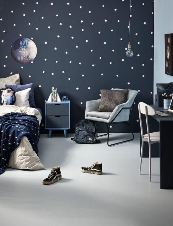 una bella camera per bambini a tema spaziale in blu scuro, grigio e bianco, con un motivo a stella incorporato e mobili blu e grigi