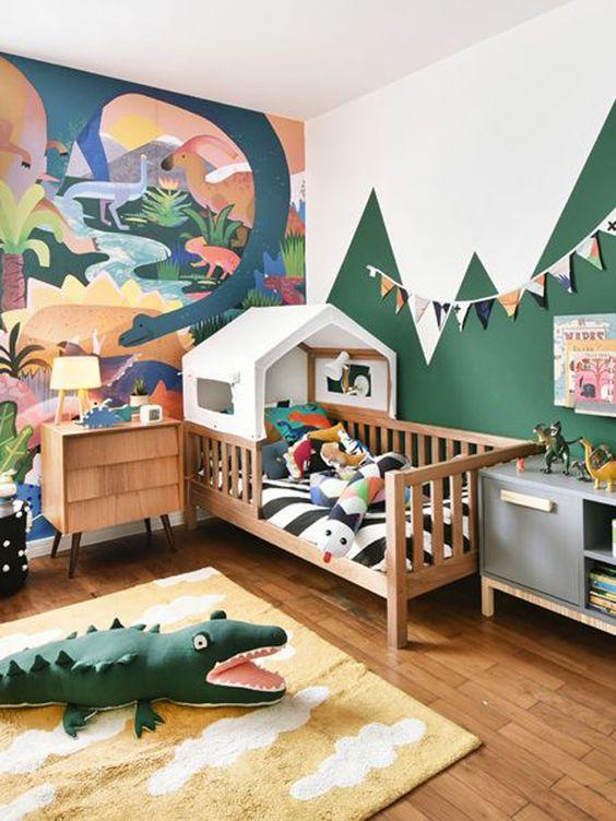 una luminosa e divertente camera da letto per bambini a tema giungla con un'opera d'arte audace, un letto a casa e giocattoli colorati ispirati alla giungla