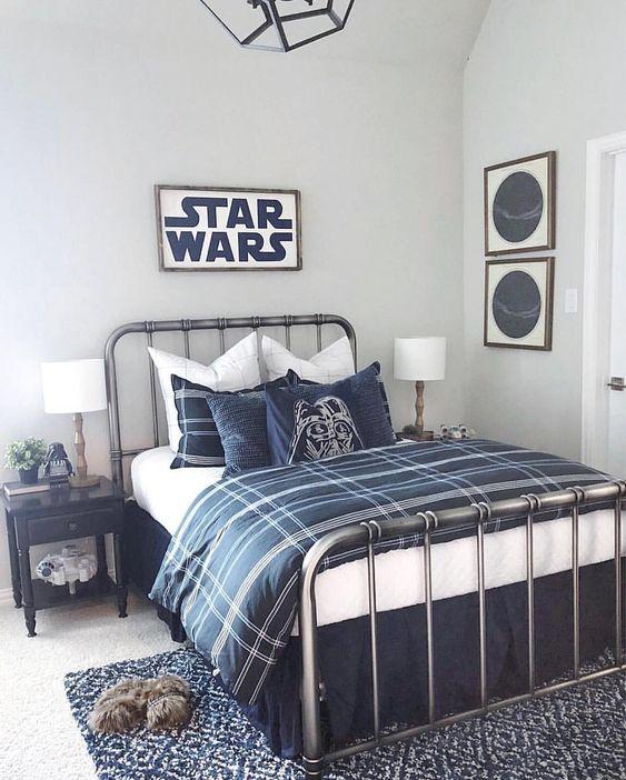 una camera da letto a tema Star Wars realizzata in bianco sporco e blu scuro, con biancheria da letto bicolore, segni, cuscini e altri piccoli tocchi nell'arredamento