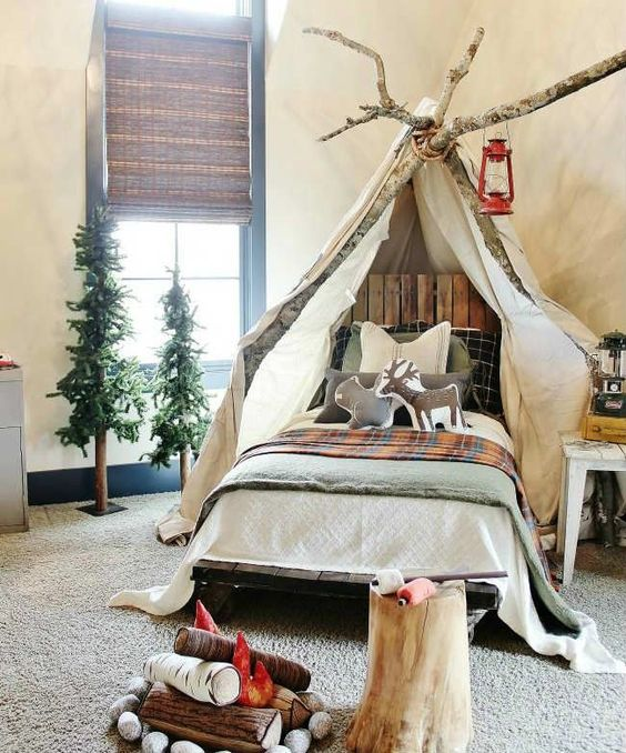 una splendida camera per bambini a tema campo con baldacchino sui rami, tende intrecciate, alberi finti e un finto caminetto