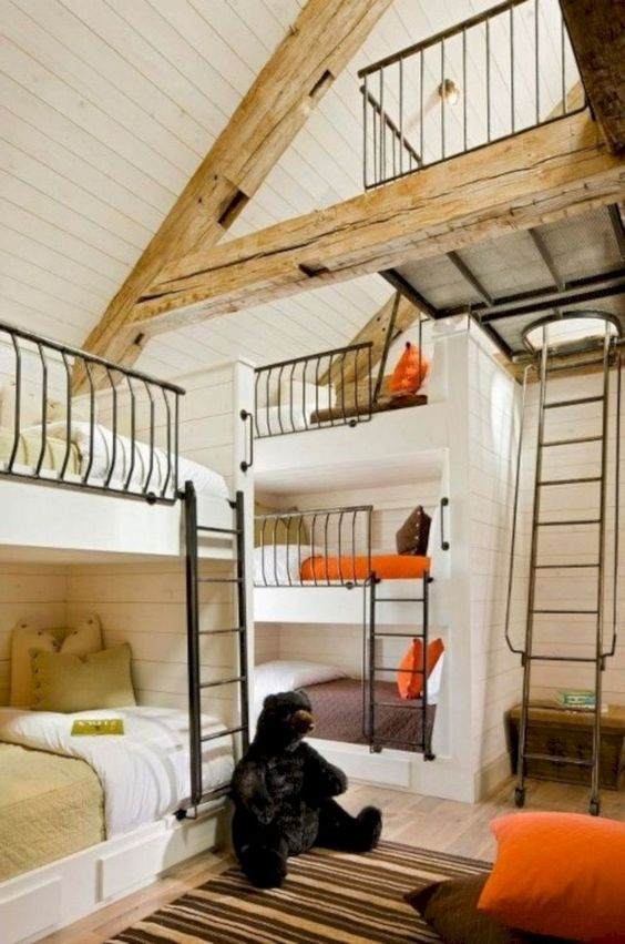 un grande asilo nido a tema capanna di tronchi fatto con verde, arancione e marrone, con letti a castello e tappeti a righe