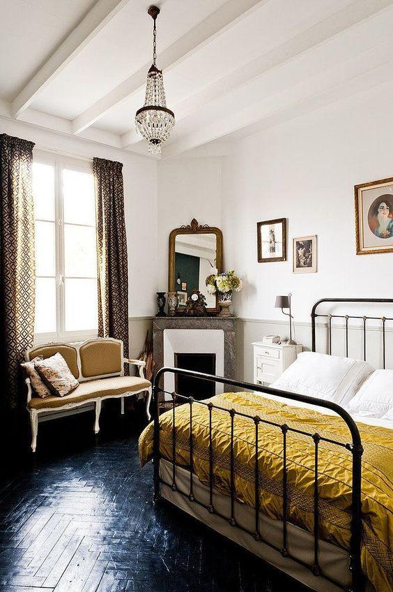 un'elegante camera da letto parigina con tende stampate, un lampadario di cristallo, un letto retrò in metallo, un divanetto chic color senape e un caminetto rivestito in marmo