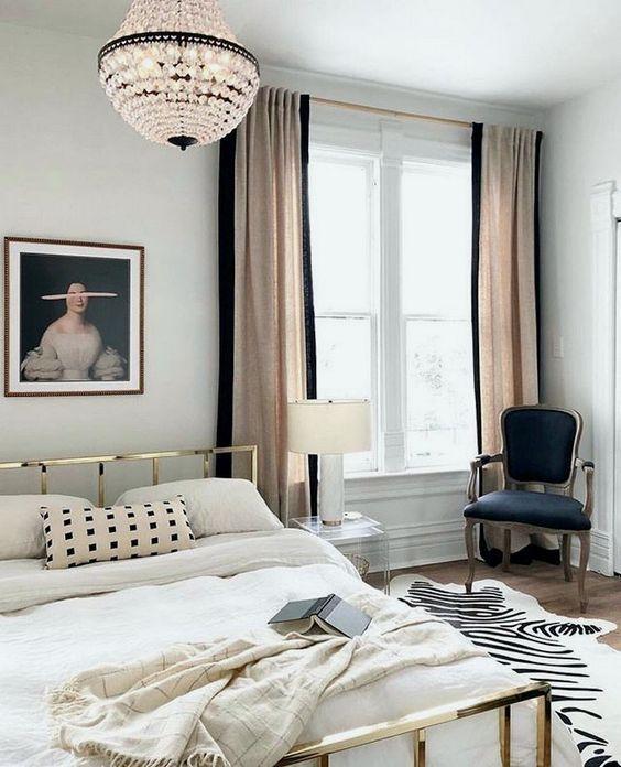 un'elegante camera da letto parigina con un letto d'oro, un lampadario di cristallo, una sedia raffinata e tende arrossate e nere