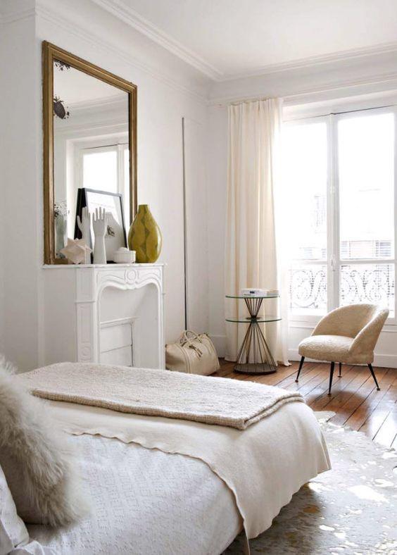 un'elegante camera da letto parigina neutra con un finto camino, uno specchio, una sedia neutra e un grande letto