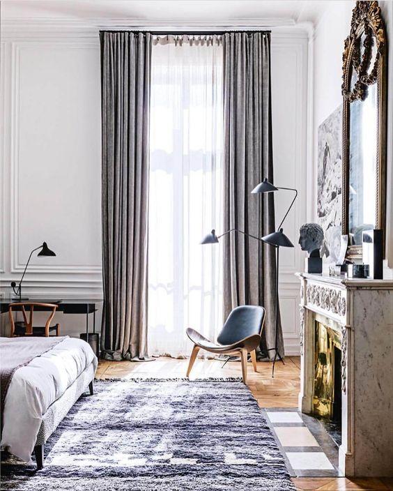 uno spazio per dormire chic con tessuti grigi, una sedia in pelle, una piccola scrivania nell'angolo, un caminetto non funzionante e un letto comodo